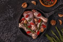 Raw chicken legs with rosemary, garlic and chilli. Royalty Free Stock Images