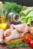 Raw chicken legs with spices and vegetables on a cutting board. Raw chicken legs with spices and vegetables on a wooden board Royalty Free Stock Photos