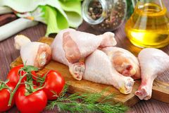 Raw chicken legs with spices and vegetables on a cutting board. Raw chicken legs with spices and vegetables on a wooden board Stock Photos