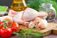Raw chicken legs with spices and vegetables on a cutting board. Raw chicken legs with spices and vegetables on a wooden board Stock Photo