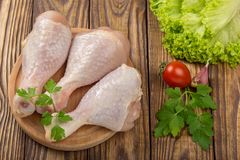 Raw chicken legs with tomatoes and garlic on a cutting board. Raw chicken legs with tomatoes and garlic on  cutting board Royalty Free Stock Images