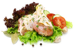 Raw chicken legs with vegetables. On a white background Royalty Free Stock Photography