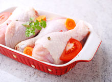 Raw chicken legs with vegetables. In a baking dish Stock Photography