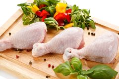 Raw chicken legs on cutting board. Raw chicken legs with vegetables on cutting board Royalty Free Stock Photography