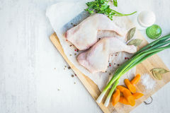 Raw chicken legs with vegetables and spices arranged on a cutting wooden board. White wood rustic background. Raw chicken legs with vegetables and spices Stock Image
