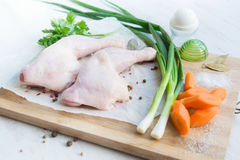 Raw chicken legs with vegetables and spices arranged on a cutting wooden board. White wood rustic background. Raw chicken legs with vegetables and spices Royalty Free Stock Image