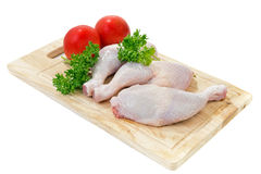 Raw chicken legs. With vegetables and spices on the chopping board Royalty Free Stock Photos