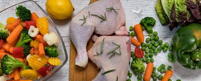 Raw chicken legs from vegetables to a wooden table. Preparation of chicken legs for vegetables, recipe - ingredients Royalty Free Stock Images