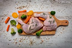 Raw chicken legs from vegetables to a wooden table. Preparation of chicken legs for vegetables, recipe - ingredients Royalty Free Stock Image