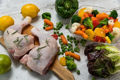 Raw chicken legs from vegetables to a wooden table. Preparation of chicken legs for vegetables, recipe - ingredients Stock Images