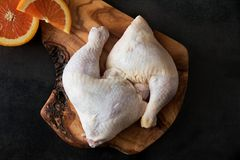 Raw chicken legs on the wooden board on a black background. Preparation Stock Images