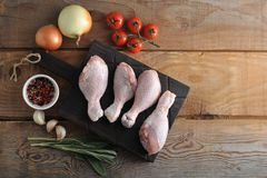 Raw chicken legs on a wooden Board, onion, garlic, spices and a. Sprig of rosemary on rustic wooden background - top view Stock Images