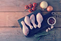Raw chicken legs on a wooden Board, onion, garlic, spices and a. Sprig of rosemary on rustic wooden background - top view Stock Photography