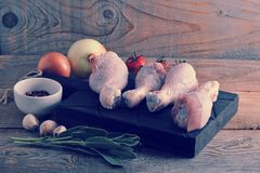 Raw chicken legs on wooden Board, onion, garlic, spices and a sp. Rig of rosemary on rustic wooden background Royalty Free Stock Photos