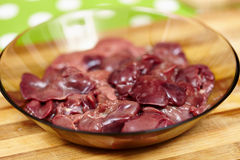 Raw chicken liver. Closeup of a plate with raw chicken liver on a wooden board Stock Photography