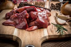 Raw chicken liver on cutting board. Selective focus Stock Photos