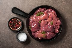 Raw chicken liver in frying pan, salt and pepper on kitchen tabl. E, top view Stock Photos