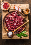 Raw chicken liver in rustic bowl with herbs and spices ingredients for cooking, composing. Top view Stock Photo