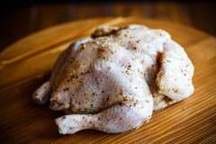 Raw chicken marinated with spices. On a wooden table Royalty Free Stock Photos