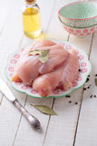 Raw chicken meat. Fresh raw chicken meat on plate on white table with bay leaves, oil. Selective focus Royalty Free Stock Photo