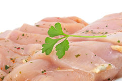 Raw chicken meat. Some pieces of raw chicken meat marinated with parsley and olive oil on a white background stock images
