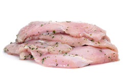 Raw chicken meat. Some slices of raw chicken meat marinated with parsley and olive oil on a white background Stock Images