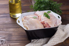 Raw  chicken meat  on wooden table. Raw chicken meat in bowl with herb  on dark painted wooden planks. Selective focus. Rustic style Royalty Free Stock Image
