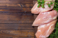 Raw  chicken meat  on wooden table. Fresh chicken meat with herb on wooden board on table . Selective focus. Rustic style Stock Photos