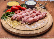 Raw chicken pieces on skewers on a chopping board with herbs vegetables sauce on wooden background close up Stock Images