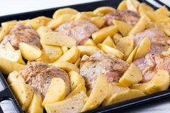 Raw chicken with raw potatoes in the form for baking. Ready to be cooked Stock Image