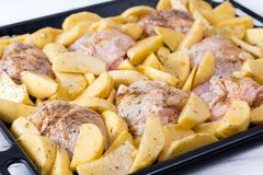 Raw chicken with raw potatoes in the form for baking, ready to be cooked. Raw chicken with raw potatoes in the form for baking Royalty Free Stock Image