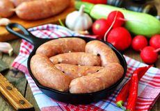 Raw chicken sausages with vegetables on a frying pan Royalty Free Stock Image