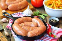 Raw chicken sausages with vegetables on a frying pan Royalty Free Stock Photo