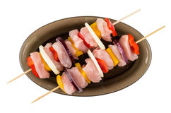Raw chicken shashlik on wooden skewers in dish on white Royalty Free Stock Images