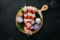 Raw chicken shish kebab with cherry tomatoes. Barbecue. On a black stone background. Top view. Free copy space stock image