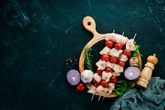 Raw chicken shish kebab with cherry tomatoes. Barbecue. On a black stone background. Top view. Free copy space royalty free stock photography