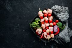 Raw chicken shish kebab with cherry tomatoes. Barbecue. On a black stone background. Top view. Free copy space royalty free stock images
