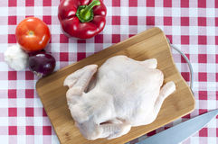 Raw chicken on table. Raw chicken on wooden board with knife Stock Photos