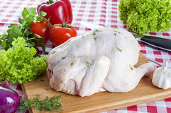 Raw chicken on table. Raw chicken on wooden board with knife Royalty Free Stock Image