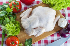 Raw chicken on table. Raw chicken on wooden board with knife and vegetables Royalty Free Stock Images