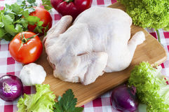 Raw chicken on table. Raw chicken on wooden board with vegetables Royalty Free Stock Photos