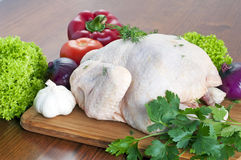 Raw chicken on table. Raw chicken on wooden board with vegetables Stock Photography
