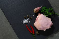 Raw chicken thigh on black stone plate. The view from the top stock photography