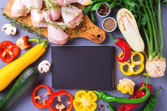 Raw chicken thighs with various vegetables ingredients. Top view Royalty Free Stock Image