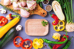 Raw chicken thighs with various vegetables ingredients. Top view Stock Images