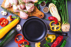 Raw chicken thighs with various vegetables ingredients. Top view Stock Photo