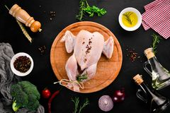 Raw chicken with vegetables and spices. Barbecue. On a black stone background. Top view. Free copy space stock photography