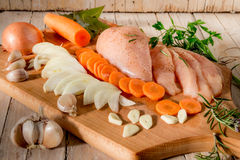 Raw chicken with vegetables and spices. Carrot bow garlic herbs Royalty Free Stock Image