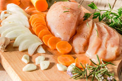 Raw chicken with vegetables and spices. Carrot bow garlic herbs Stock Photos