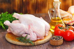 Raw chicken with vegetables and spices before cooking. Uncooked chicken with vegetables and spices before cooking Royalty Free Stock Images
